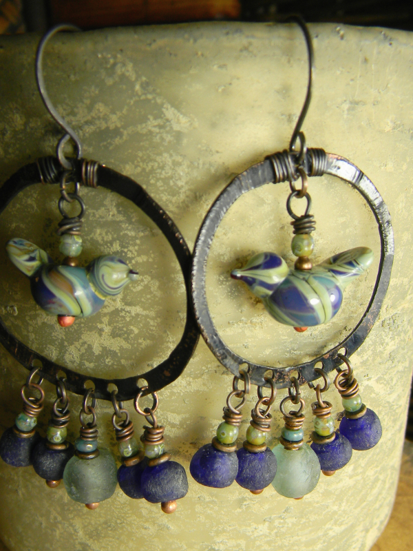 Artisan bird beads in hammered copper hoops by Gloria Ewing.