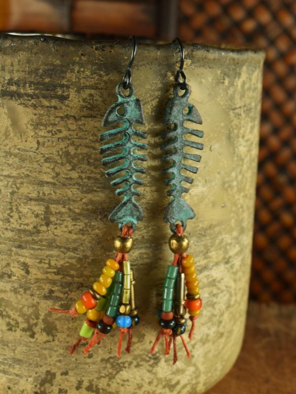 Patina fish skeleton with beaded fringe by Gloria Ewing.