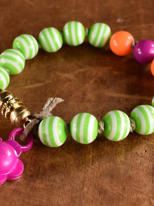 Striped acrylic beaded bracelet with flower charm by Gloria Ewing.