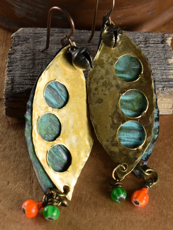 Layered metal with cut outs and African dangles by Gloria Ewing.