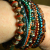 Multi-strand statement bracelet in luscious teal and rust beads.