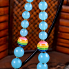 Blue jelly acrylic beaded necklace with rainbow accent by Gloria Ewing.