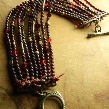 Beaded bracelet in garnet red and bronze by Gloria Ewing.