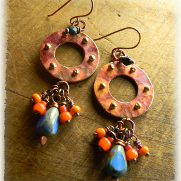 Orange patinaed copper hoop earrings by Gloria Ewing.