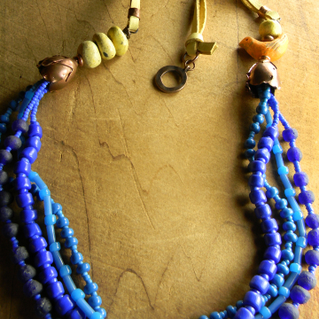 Multi-strand blue and pale yellow design with orange bird.