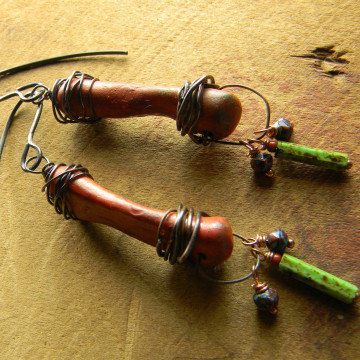 Copper wire wrapped red clay earrings by Gloria Ewing.